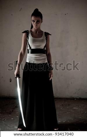 Beautiful woman holding a long shining steel ceremonial sword - stock photo