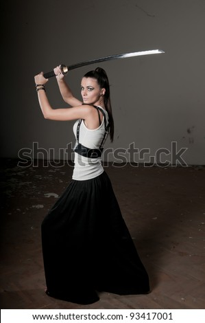 Beautiful woman holding a long shining steel ceremonial sword above her head - stock photo