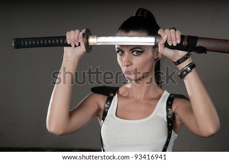 Beautiful Woman Holding A Long Shining Steel Ceremonial Sword In Front