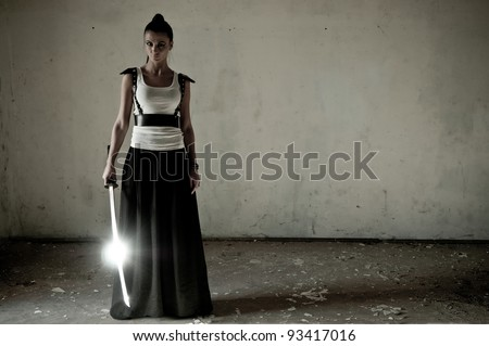 Beautiful woman holding a long shining steel ceremonial sword with copyspace.