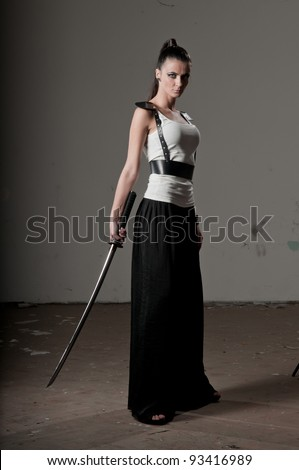 Beautiful woman holding a long steel sword - stock photo