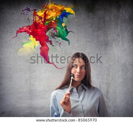 Beautiful woman holding a paintbrush with colors coming out from it - stock photo
