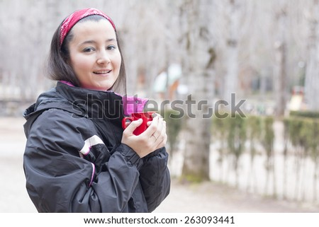 Beautiful woman holding a red mug with coffee wearing mountain cloth