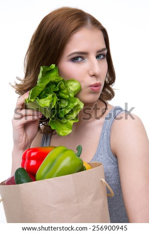 Beautiful woman holding a shopping bag full of groceries - stock photo