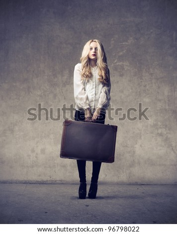 Beautiful woman holding a suitcase - stock photo