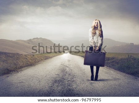 Beautiful woman holding a suitcase on a countryside road - stock photo