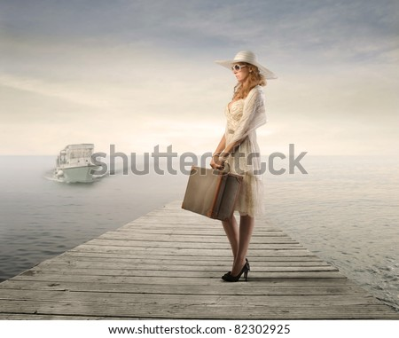 Beautiful woman holding a suitcase on a pier with motorboat approaching