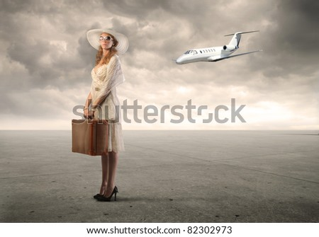 Beautiful woman holding a suitcase with airplane in the background