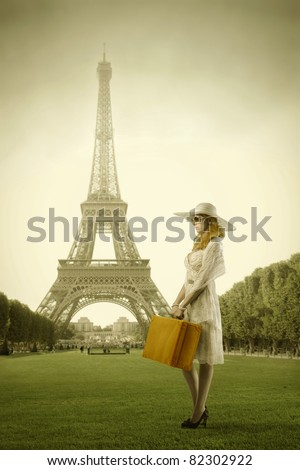 Beautiful woman holding a suitcase with Eiffel Tower in the background