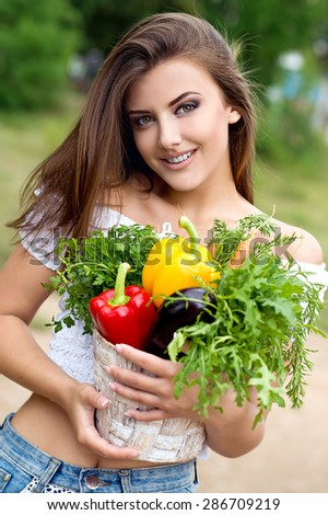 Beautiful woman holding a vegetable - parsley, pepper, eggplant,carrots, arugula in basket on green background summer nature. - stock photo