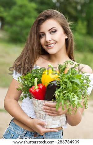 Beautiful woman holding a vegetable - parsley, pepper, eggplant,carrots, arugula in basket on green background summer nature.