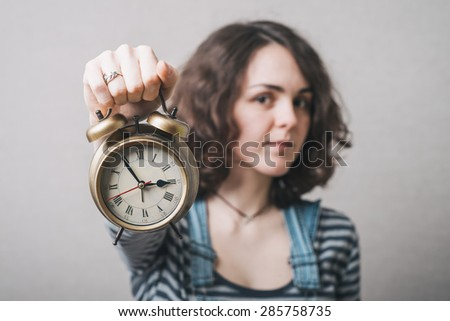 beautiful woman holding alarm clock in hand, dressed in a suit