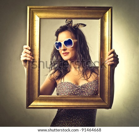 Beautiful woman holding an empty frame - stock photo