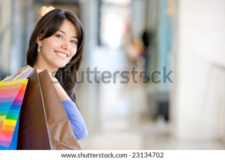 Beautiful woman holding bags in a shopping mall - stock photo