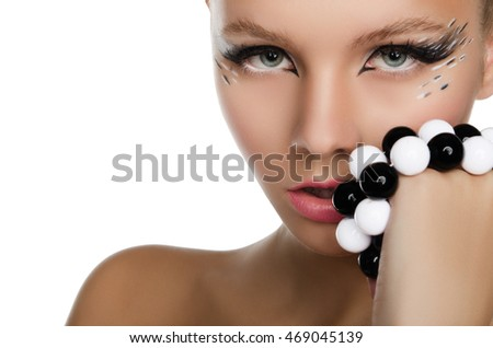 beautiful woman holding black and white beads at mouth isolated on white