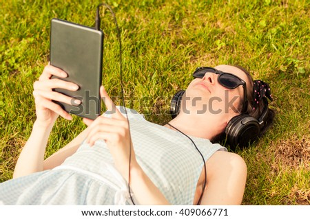 Beautiful woman holding digital tablet in park on sunny day and lying on grass as outdoor relaxation concept - stock photo