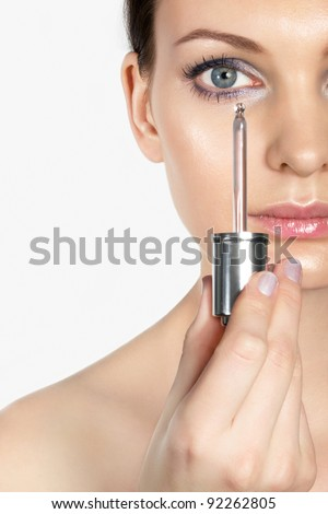 Beautiful woman holding dropper with cream