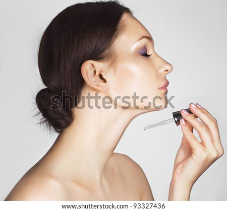 Beautiful woman holding dropper with cream - stock photo