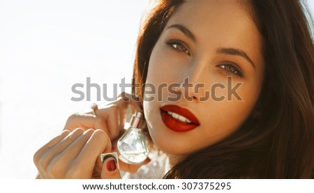 Beautiful woman holding Fragrance . Red lips and nails. Studio shot. Copy space for your text. Horizontal - stock photo