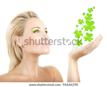 Beautiful woman holding fresh clover plant  in hand, sensual female portrait isolated on white background, cute girl with bright green makeup, st.Patrick's day holiday - stock photo