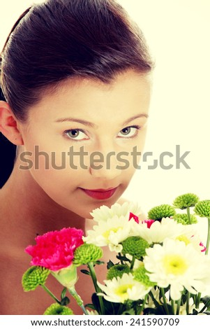 Beautiful woman holding fresh spring flowers - stock photo
