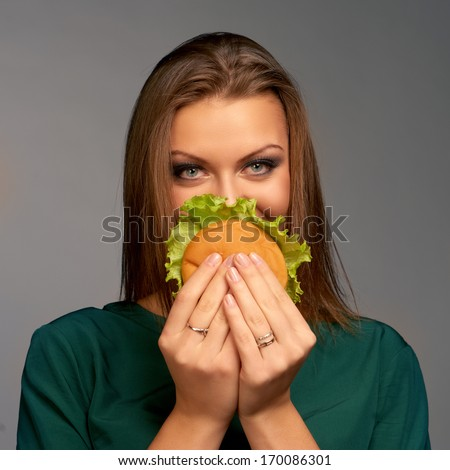 Beautiful woman holding hamburger - stock photo