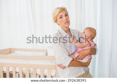 Beautiful woman holding her baby girl at home in bedroom - stock photo