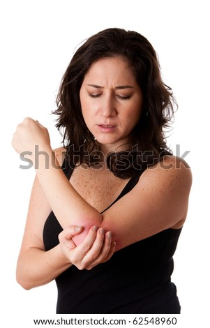 Beautiful woman holding her elbow with pain and arm ache,wearing a sporty black tank top, isolated. - stock photo