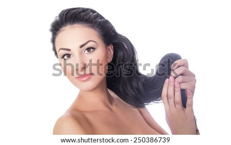 Beautiful woman holding her hair, isolated on white background, studio shot. - stock photo