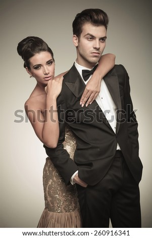Beautiful woman holding her husband from ther back while looking at the camera. - stock photo