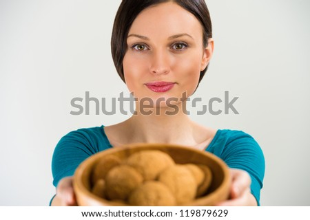 Beautiful woman holding hot fresh smelling oat cookies and smiling at camera - stock photo