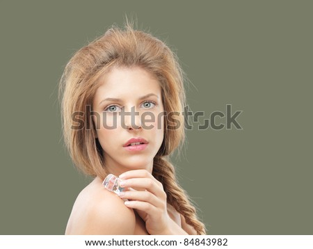 beautiful woman holding ice cube on shoulder - stock photo