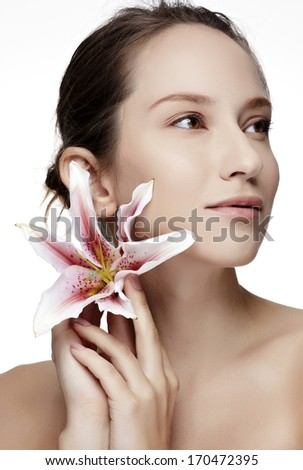 Beautiful woman holding lilly flower in her hands on the white background-Studio Shot.