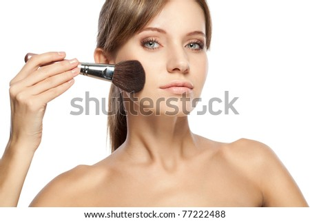 beautiful woman holding makeup brush over white