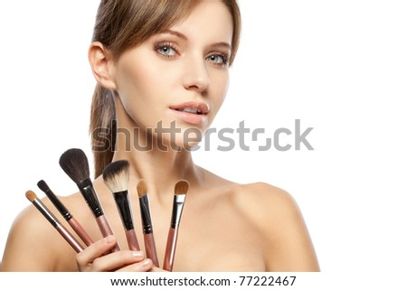 beautiful woman holding makeup brushes set over white