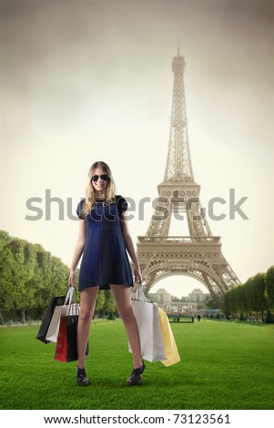Beautiful woman holding many shopping bags with Eiffel Tower on the background