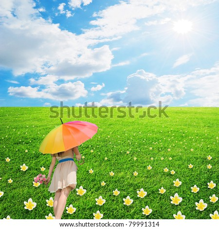 Beautiful woman holding multicolored umbrella on flower grass and cloud sky