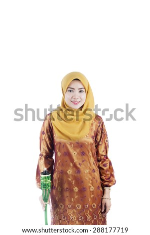 Beautiful woman holding pelita or oil lamp standing on isolated white background, Feast of Aidilfitri concept - stock photo