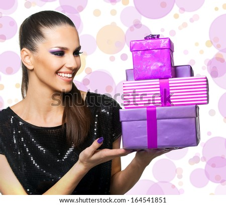 Beautiful woman holding purple gifts - stock photo