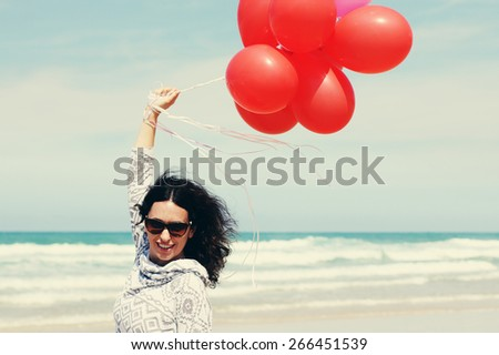 beautiful woman holding red balloons  - stock photo