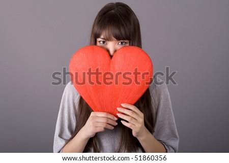 Beautiful woman holding red heart - stock photo