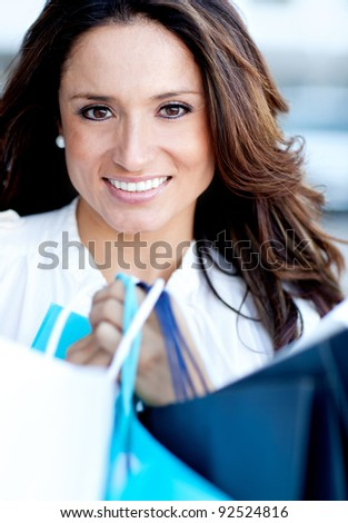 Beautiful woman holding shopping bags and smiling - stock photo
