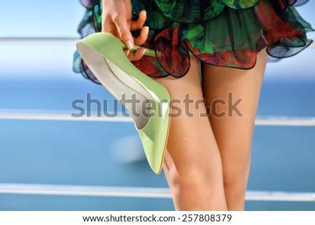 beautiful woman holding stiletto high heel shoes wearing green dress standing - stock photo