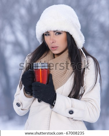 Beautiful woman holding thermal mug in snowy winter outdoors - stock photo