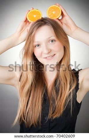 Beautiful woman holding two halfs of orange on her head like Mickey Mouse ears - stock photo