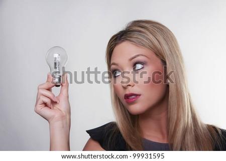 beautiful woman holding up a light bulbs - stock photo