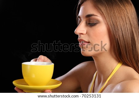 Beautiful woman holding yellow tea cup and saucer - stock photo