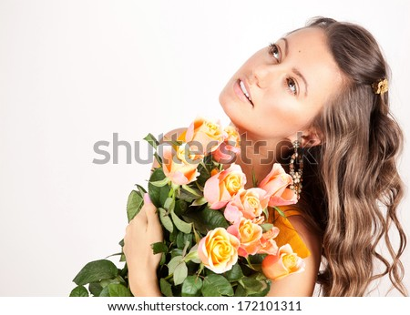 Beautiful woman hugging a large bouquet of flowers, smelling fragrant pink rose.