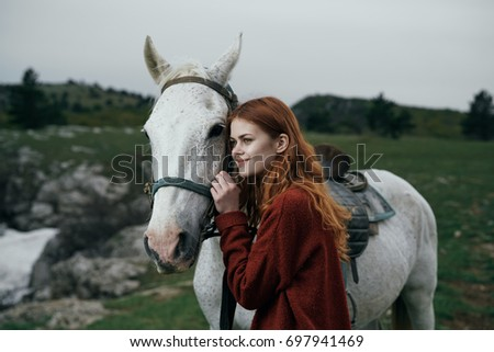 Beautiful woman hugging a white horse in the mountains, nature.