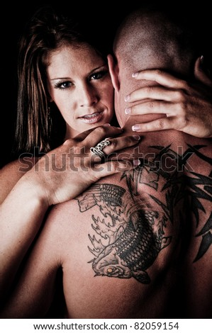 Beautiful Woman hugging and looking over the shoulder of a man - stock photo